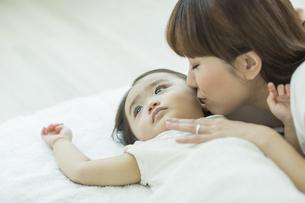 横になる赤ちゃんにキスをする母親の写真素材 [FYI01622753]
