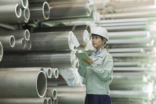 タブレットPCを持って働く作業服の女性の写真素材 [FYI01622788]