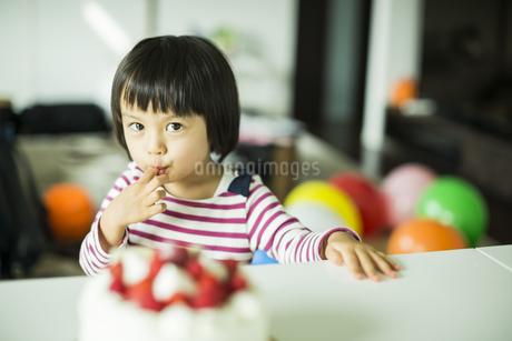 ケーキのクリームを舐める女の子の写真素材 [FYI01622798]