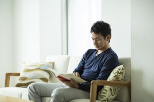 ソファーで読書をする男性の写真素材 [FYI01622803]