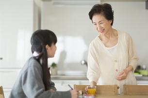 テーブルで勉強する孫と会話をする祖母の写真素材 [FYI01622810]