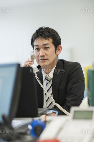 デスクで電話をするビジネスマンの写真素材 [FYI01622812]