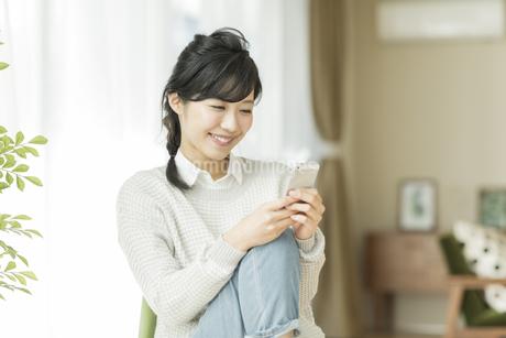 椅子に座って携帯電話を見る女性の写真素材 [FYI01622813]