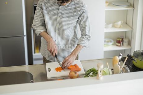 キッチンで野菜を切る若い男性の写真素材 [FYI01622829]