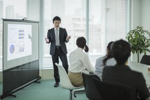 プロジェクターを使用した会議で説明をするビジネスマンの写真素材 [FYI01622841]