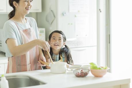 キッチンで料理をする母親に寄り添う女の子の写真素材 [FYI01622855]