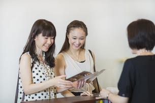 エステサロン受付カウンターで話す若い女性の写真素材 [FYI01622880]