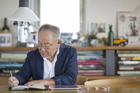 手帳に記入するシニア男性の写真素材 [FYI01622886]