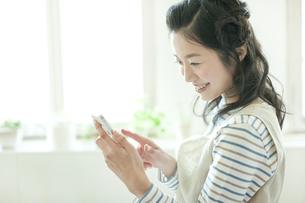ベンチソファーに座りスマートフォンを操作する若い女性の写真素材 [FYI01622895]