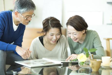 思い出のアルバムを見て懐かしむ家族の写真素材 [FYI01622899]