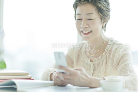 携帯電話のメール操作をする中高年女性の写真素材 [FYI01622925]