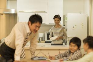 キッチンで家事をしながら家族を見守る母親の写真素材 [FYI01622929]