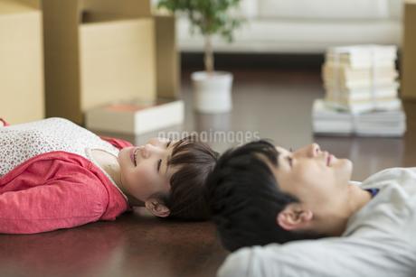 床に寝転ぶ若いカップルの写真素材 [FYI01622949]