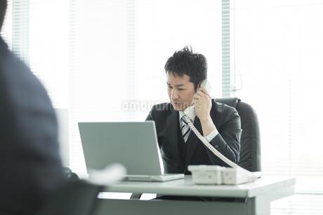 デスクで電話をするビジネスマンの写真素材 [FYI01622952]