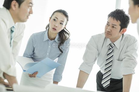 打ち合わせで真剣に話しを聞くビジネスマンとビジネスウーマンの写真素材 [FYI01622959]