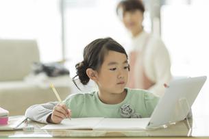 タブレットPCを見ながら勉強をする女の子の写真素材 [FYI01622964]