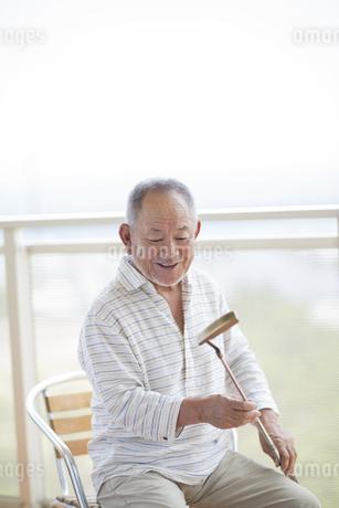バルコニーでゴルフクラブの手入れをするシニア男性の写真素材 [FYI01622981]