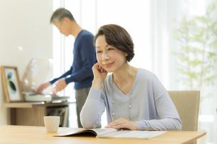テーブルで雑誌を読むシニア女性の写真素材 [FYI01622983]