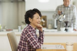 テーブルに座り笑顔のシニア女性の写真素材 [FYI01622998]