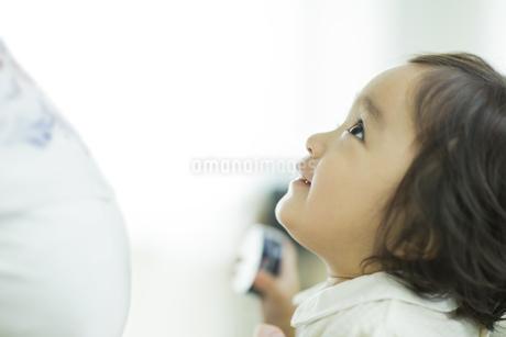 妊婦の母親を見上げる赤ちゃんの写真素材 [FYI01622999]