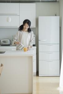 キッチンでコーヒーをカップに注ぐ女性の写真素材 [FYI01623002]