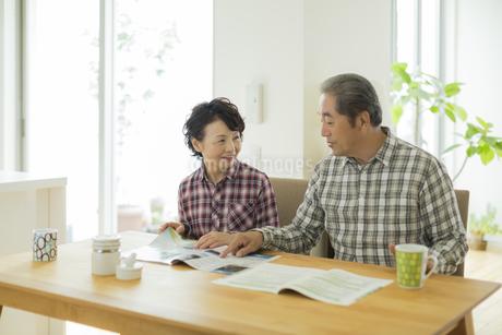パンフレットを見ながら会話をするシニア夫婦の写真素材 [FYI01623006]