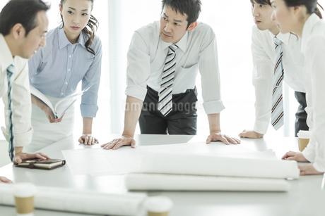 打ち合わせで真剣に話しを聞くビジネスマンとビジネスウーマンの写真素材 [FYI01623030]