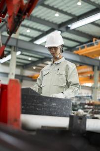 機械を操作する作業服の男性の写真素材 [FYI01623033]