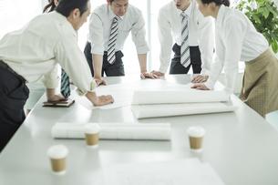 テーブルに図面を広げて打ち合わせをするビジネスマンとビジネスウーマンの写真素材 [FYI01623034]