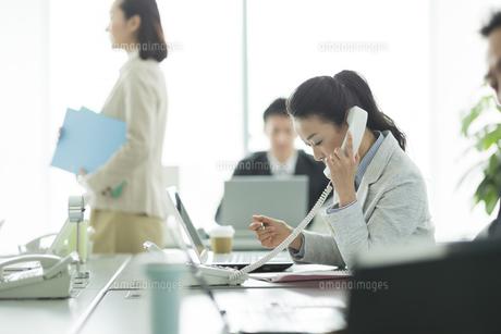 デスクで電話をするビジネスウーマンの写真素材 [FYI01623045]