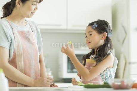 母親に切った野菜を見せる女の子の写真素材 [FYI01623049]