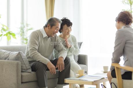 商談をするシニア夫婦とビジネスウーマンの写真素材 [FYI01623056]