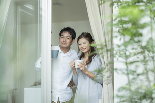 窓辺で外を眺める夫婦の写真素材 [FYI01623057]