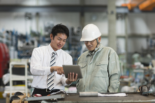 タブレットPCを見ながら打ち合わせをする作業員とビジネスマンの写真素材 [FYI01623066]