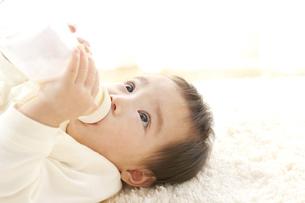 寝転びミルクを飲む赤ちゃんの写真素材 [FYI01623077]
