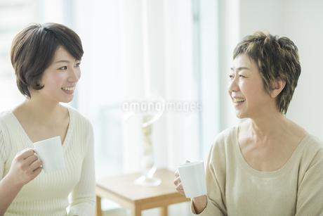 お茶を飲みながら笑顔で会話をする母娘の写真素材 [FYI01623088]