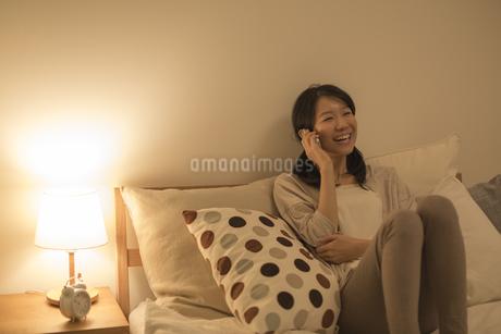 ベッドに座って電話をする女性の写真素材 [FYI01623090]