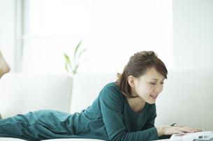 ソファに寝転んで雑誌を読む女性の写真素材 [FYI01623093]
