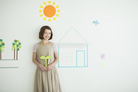 壁のイラストの前に立つ双葉を持った女性の写真素材 [FYI01623096]