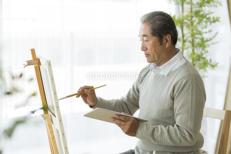 キャンバスに絵を描くシニア男性の写真素材 [FYI01623123]