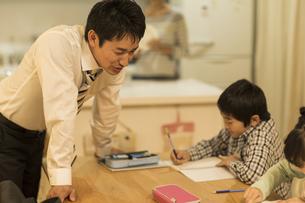 子供たちの勉強を見る父親の写真素材 [FYI01623140]