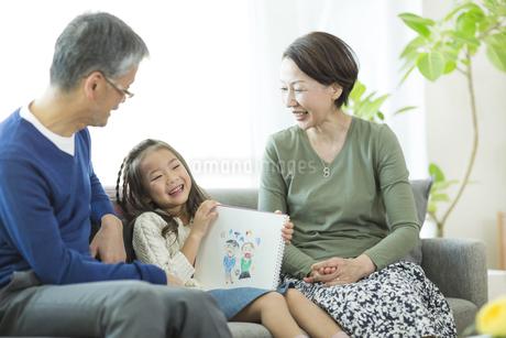 祖父母にスケッチブックを見せる女の子の写真素材 [FYI01623145]