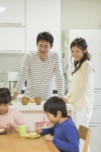 キッチンから子供たちを見守る夫婦の写真素材 [FYI01623150]