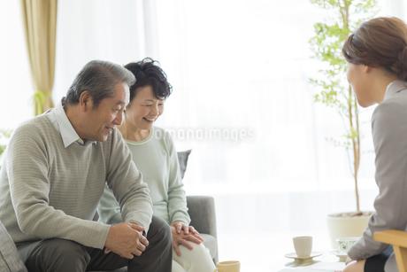 商談をするシニア夫婦とビジネスウーマンの写真素材 [FYI01623153]
