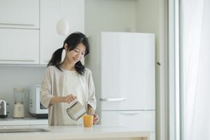 キッチンでコーヒーをカップに注ぐ女性の写真素材 [FYI01623177]