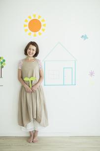 壁のイラストの前に立つ双葉を持った女性の写真素材 [FYI01623185]