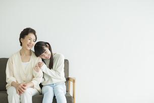ソファーに座って寄り添う祖母と孫の写真素材 [FYI01623188]