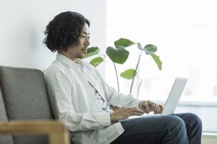ソファーに座ってパソコンをする男性の写真素材 [FYI01623189]