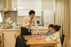子供たちの勉強を見る父親の写真素材 [FYI01623201]