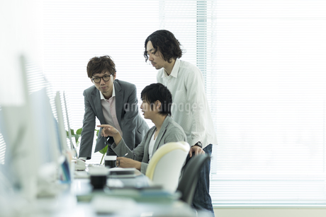 パソコンのモニターを見ながら打ち合わせをするビジネスマンの写真素材 [FYI01623212]